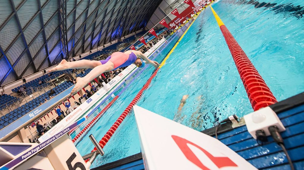 Swimmer diving off block into swimming lane